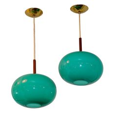 "Pair of Turquoise Glass Pendants by Prescolite  USA  1960's  Pair of turquoise or seafoam colored glass pendants in shape of oblate spheroid by Prescolite of California. Each hangs from vinyl coated wire and has a dark wood stem (possibly walnut or teak) and original brass ceiling caps (5.5"" in diameter). Each pendant takes a single 75 watt bulb. Length of cord can be increased or shortened."