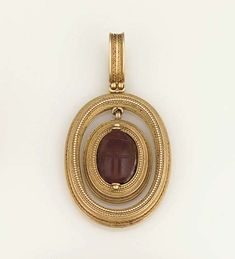 An archaeological revival gold and cornelian pendant, by Robert Phillips The central carved cornelian scarab within an Etruscan design oval border, suspended within a matching larger frame, to a beaded pendant loop, circa 1880 The reverse with applied maker's plaque for Robert Phillips
