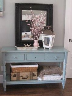 Entryway Design - lantern on the table, framed art and blankets folded in baskets