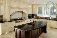 This bright and spacious kitchen has the perfect mix of dark and light colored design aspects to create a rich and elegant atmosphere. The granite featured is Platinum Bahia, a fairly consistent chocolate colored stone, with platinum colored clusterings.