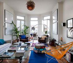 Decoração ousada, luz natural, sala de estar, tapete azul, cadeira laranja e acessórios coloridos.