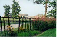 Landscaping along fence.   Hartsell Brothers Fence Co., Inc - Aluminum Ornamental Fence