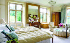 Combe House bedroom interior. Plush furnishings and thick drapes. The perfect bedroom.
