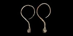 VIKING SILVER EARRING PAIR. 9th-10th century AD. A matched pair of earrings, each a round-section hook and twisted shaft with polyhedral terminal, a crescentic stamp to each of the vertical faces