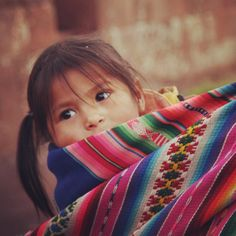 Little girl, carried on her mother's back in Peru. @info_peru