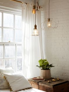 "Handmade lamps, crafted from a lampshade found in Ibiza, hang by the couple's sofa bed. The planter on the table ""is a pot molded to look like a sack. I found it at Anthropologie and fell in love with it,"" Marshall says. 