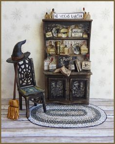 """1/4 """" Something Wicked Vignette - This 1/4"""" scale kit includes the hutch, chair, rug, bottles, books and assorted accessories, artwork and instructions. Finished Size:  Hutch approx 1"""" w x 1 3/4"""" h. Chair approx 1/2"""" w x 1"""" h"""