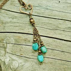 Three dangles of turquoise beads swing on chains below hand crafted and hammered copper bear hug heart. Antiqued copper chain is accented with