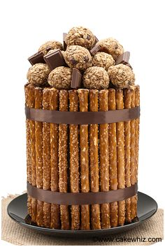 A stunning PRETZEL CAKE, which is basically composed of a double decker chocolate cake frosted in chocolate buttercream and then covered in pretzel rods and finally topped off with choco peanut butter balls! From cakewhiz.com