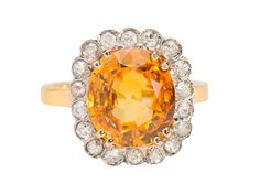 Good Day Sunshine - Orange Sapphire Diamond Ring. A gorgeous glowing orange sapphire of 3.87 carats will virtually light up your surroundings with its eye popping sunny color. Think of an expanse of sunflowers rearing their golden heads as a cool breeze ripples through the field. A surround of 18 single cut diamonds caresses the sapphire in a bright and shimmering embrace. All in a platinum-topped mounting of 14k yellow gold.  Circa 1920.