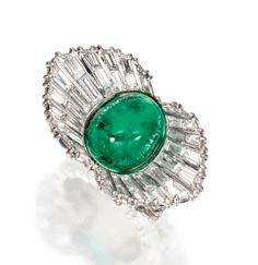 PLATINUM, CABOCHON EMERALD AND DIAMOND RING, STERLÉ, PARIS, CIRCA 1950    Centering upon a cabochon emerald measuring approximately 12.8 by 10.4 mm., flanked by fluted upturned panels set with baguette diamonds, the shank set with baguette diamonds and platinum reeding at the sides, the total diamond weight approximately 6.00 carats, size 4¾, signed Sterlé, numbered 8013, French assay mark.