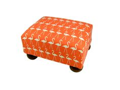 This small fabric covered footstool is a charming addition to any beach house room, highlighted with a group of white dancing flamingos on a bright orange background. Made in the USA. Check out the co