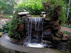 Stand alone stone waterfall.  Really love how it's the main focal point in an area that could use some height in a flat part of the garden. Don't have a natural hill for a water feature?....create it!