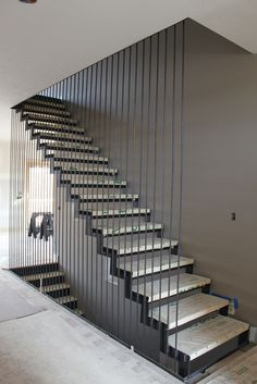 """Caliper Studio designed, fabricated and installed this custom stair for a client in Nebraska. The top flight of the stair is composed of 1/2"""" thick steel plate stringers clamped around butcher block red oak treads. The outside stringer is hung with 1/2"""" diameter rods at 4"""" on center. All steel components are blackened.   Special thanks to Advanced Design and Construction of Omaha for install assistance. Treads by Ethan Ames."""