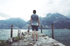 man standing on gray concrete dock facing body of water and mountains at daytime Stone jetty on a cloudy day Michael Phelps, Saint Laurent Paris, New Travel, Travel Goals, Beyonce, Travel Around The World, Around The Worlds, Vogue Magazin, Encouragement