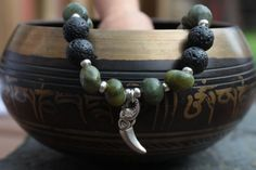 What you see is what you get - this is the only one of this bracelet I will make! Get it before its gone! - Natural shaped sanguaro jasper beads. - 8mm black lava stone beads. - Silver tone elephant head/tusk charm. - Silver tone glass spacer beads. - 6.5 Inches un-stretched (approximately). This bracelet best fits people with a small/medium frame. - Ships from Canada.  Get back to nature with this jungle-inspired bracelet that features genuine jasper and lava stone (a natural diffuser)…