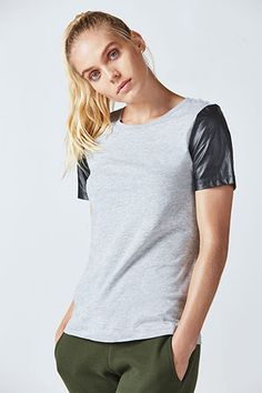 Master the mixed media trend by wearing our faux leather sleeve t-shirt. Balance structural fabrics with a soft jersey body. A faux leather back band keeps things exciting from the other side.