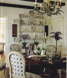 Dining room with a few dark wood beams, dark wood table, white plate rack and white washed chairs. Light and bright.