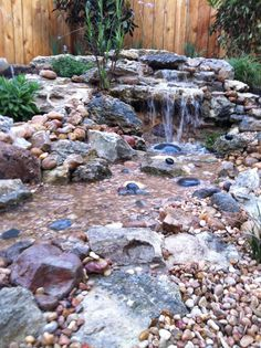 small waterfall in backyard garden. it empties into a small stream and is also illuminated with LED lighting at night