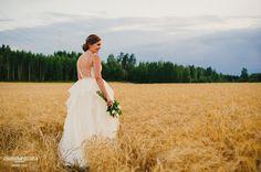 Lace wedding dress, open back, straps, bride in a field. Dress by Pukuni (www.pukuni.fi)