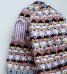 The link does not lead to it but this mitten design looks like SpillyJane's on Ravelry. http://www.ravelry.com/patterns/library/cupcake-mittens