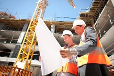Stock Photo : Construction workers looking at blueprints on construction site