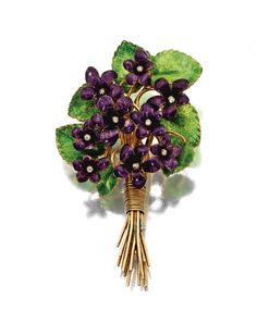 AN ENAMEL VIOLET BROOCH, CIRCA 1900.  Depicted as a spray of violets, the petals and leaves applied with translucent purple and green enamel, the center of each flower accented with an old-mine diamond, mounted in gold and silver.
