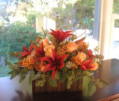 "Lush Low Fall Centerpiece in aa 7"" Low Willow Container featuring Seeded Eucalyptus, Peach Versilia Roses, Black Out Lilies, Orange Wax Flower and Curly Willow Branches"