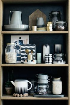 Great combination of decorative pottery like storage jars, teapots and cups on shelf!