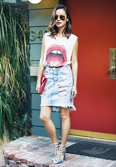Jamie Chung wears a graphic muscle tank, distressed denim skirt, lace-up heels, and a red clutch