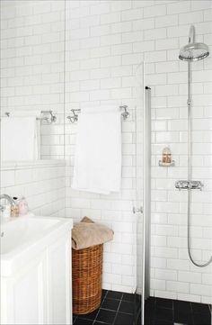 Badrummet är inrett med fasetterat kakel. En infälld spegel täcker väggen ovanför handfatet vilket g...