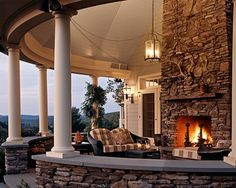 Beautiful circular porch with fireplace - wide stone enclosure adds seating - I would scatter cushions along that ledge and even include some filmy drapes along a long curved rod - pulled back to the wall when not in use. Tiny lights scattered up into the turret would make for an incredible party space!