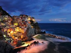 A scene of the tiny village of Manarola on the Cinque Terre coast of Italy.  I camped on this spot for some time waiting for the right balance of light as the sun set.  I was rewarded with many great shots of the late afternoon and even in moonlight.  This long exposure captures the essence of the village with the locals all joining for a party near the boat ramp. Nikon D700, Nikon 14-24mm lens, 8 sec exposure