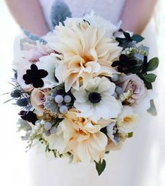 Winter wedding bouquet with dahlias, anemones, roses, and thistle by QuatreCoeur for a rooftop wedding in New York City.