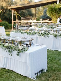 make your wedding buffet feel less like a cafeteria with a little extra floral garlands draped on the tables