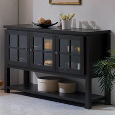 Defined by its three glass-front doors and clean-lined design, this handsome wood buffet cabinet brings sophisticated flair to your entertaining area. Its solid finish is perfect set against a crisp white wall for a contrasting look, while its understated silhouette blends effortlessly into any casual space. Lean into this piece's versatile appeal by adding it to a crisp contemporary dining room alongside a glass-top table surrounded by ladder-back side chairs. Top this piece off with a c...