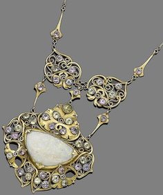 An early 20th century Arts and Crafts gem-set pendant necklace, by A.H. Anderson for the Elverhoj Colony. The wide navette-shaped plaque set with a triangular-shaped opal, in closed back-setting, within an intricate openwork scrolling surround accented by circular-cut gemstones including sapphires, chrysoberyl, and aquamarine, suspended from two similar plaques, to a figaro-link chain, signed Elverhoj, lengths: pendant 6.5cm, chain 45.8cm. Via Bonhams.