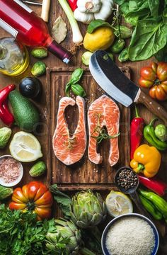 Stock image of 'Dinner cooking ingredients. Raw uncooked salmon fish with vegetables, rice, herbs, lemon, spices and bottle of rose wine over rustic wooden board, top view, vertical composition'