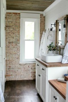 Brick wall in bathroom - love the white cabinets and butcher block countertops, wood ceiling, shiplap walls