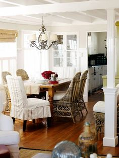 Relaxing dining room - slipcovered chairs, wicker chairs, white walls, wood floors, bamboo shades, wood table