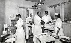 1900 Three surgeons and two nurses wearing medical uniforms performing surgery on a patient in an operating room.  Courtesy National Library of Medicine.