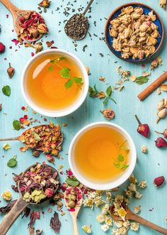 #Two cups of healthy herbal tea  Two cups of healthy herbal tea with mint cinnamon dried rose and camomile flowers in spoons over blue background top view