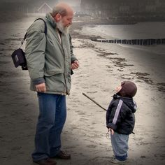 A grandson and his grandfather, having a quite moment one winter morning at the beach.