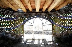 """This is the interior of an Earthship home. The self sustanible home allows you to """"live off the grid"""", the homes maintain an interior temp. of 70-72F (22C) year round using the homes mass. ( See site), The walla are made with compasted earth filled tires, but here,concrete,then  glass bottles in the wall  allowing soft light to come in the room while insulating the home. Cost range $7000- 70,000.00 depending on life style. Interesting idea and earth friendly."""