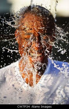 The picture was taken with a fast shutter speed to show the water dropping over his head.