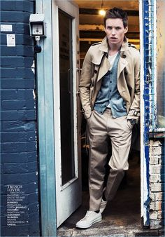 A stylish vision, Eddie Redmayne wears a Burberry trench coat, tee, and cardigan sweater. Redmayne also sports Brunello Cucinelli pants and Alexander McQueen sneakers.