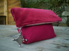 Folding clutch with metal 'pendant' feature. Zipper closure. Features Red Jute and velvet. unique model.