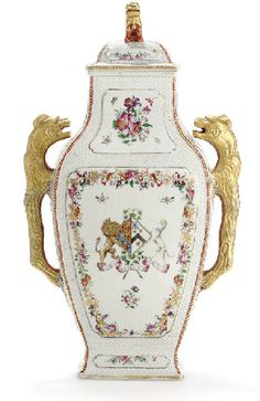 A LARGE FAMILLE ROSE ARMORIAL VASE AND COVER  CIRCA 1760  Of flattened baluster form and basketweave molded, decorated front and back with a panel centering the arms of Fitzroy impaling Cosby above the motto ET DECUS ET PRETIUM RECTI within a garland of flowers and gilt bamboo, flanked by two bois-simulé handles, the cover with Buddhistic lion finial  20¼ in. (51.4 cm.) high