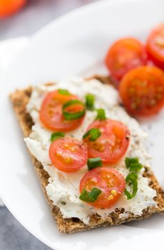 RYVITA Mediterranean Herb topped with herb and garlic cream cheese, sliced cherry tomatoes, green onions and freshly cracked black pepper
