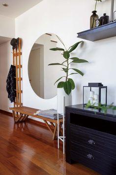 En el recibidor de un tríplex, espejo circular, perchero y banco de petiribí (Net Muebles). Además, macetero de hierro de VK Home.